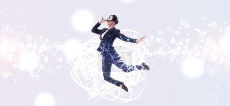 Photo pour Prise de vue panoramique de femme d'affaires en réalité virtuelle casque sautant sur fond gris avec abstrait illustration cyberespace - image libre de droit