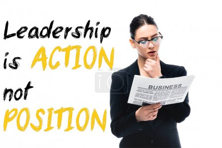 Photo for Thoughtful businesswoman reading newspaper near leadership is action not position lettering isolated on white - Royalty Free Image