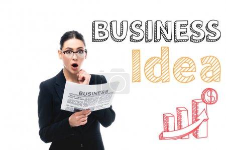 Photo pour Choqué femme d'affaires regardant caméra tout en tenant journal près de lettres idée d'affaires, graphiques et signe dollar isolé sur blanc - image libre de droit
