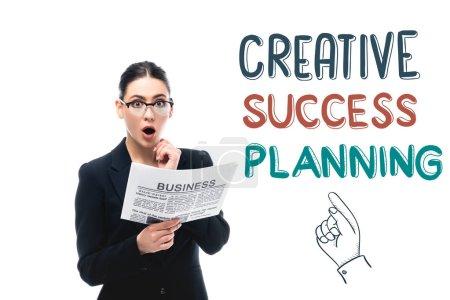 Photo pour Surpris femme d'affaires regardant caméra tout en tenant journal près de succès créatif planification lettrage et pointant la main isolé sur blanc - image libre de droit