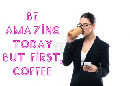 Photo for Young businesswoman using smartphone and drinking coffee to go near be amazing but first coffee inscription isolated on white - Royalty Free Image