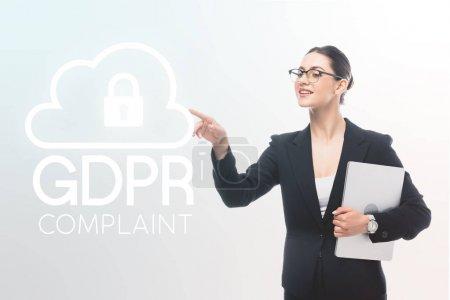 Photo pour Attrayant femme d'affaires tenant ordinateur portable et pointant avec le doigt à gdpr conforme icône de verrouillage de sécurité sur fond gris - image libre de droit