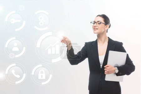 smiling businesswoman holding laptop and pointing with finger at safety icons and multimedia pictograms on grey background