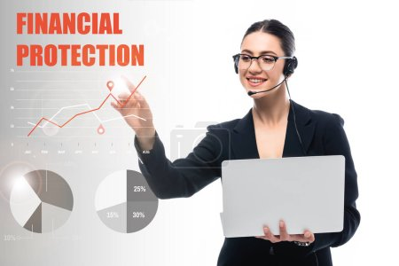 Foto de Operador del centro de llamadas sonriente sosteniendo la computadora portátil y señalando con el dedo en las letras de protección financiera y las infografías sobre fondo gris y blanco - Imagen libre de derechos