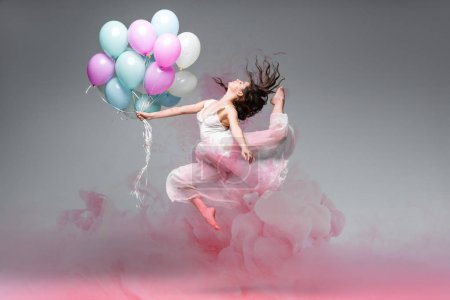 Photo for Beautiful ballerina dancing with festive balloons near pink smoke splashes on grey background - Royalty Free Image