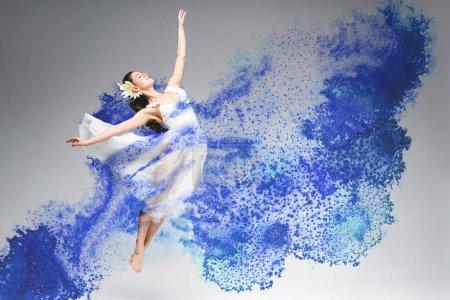 Photo pour Jeune ballerine en robe blanche dansant en peinture bleue éclaboussures sur fond gris - image libre de droit