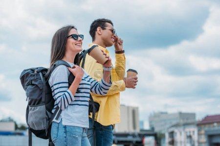 Photo pour Vue de côté de la femme sourite avec la tasse et le sac à dos de papier près de l'ami bi-racial - image libre de droit