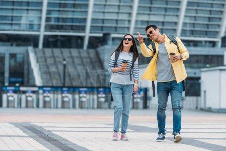 Photo pour Homme biracial pointant avec le doigt près de la femme de sourire avec la tasse et le sac à dos de papier de café - image libre de droit