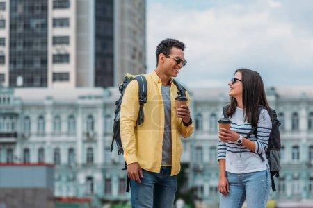 Photo pour Femme regardant sur l'ami bi-racial et souriant avec la cuvette et le sac à dos de papier de café - image libre de droit