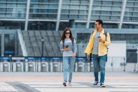 Photo pour Femme marchant près de l'ami bi-racial avec la tasse et le sac à dos de papier de café - image libre de droit
