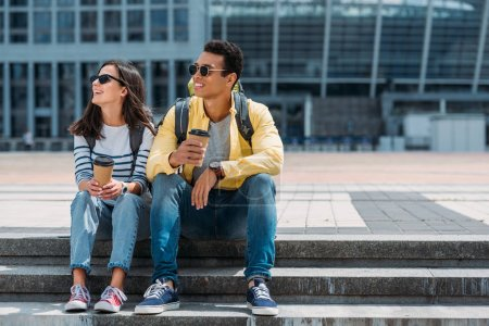 Photo for Interracial tourists with backpacks sitting on stairs with paper cups of coffee and looking away - Royalty Free Image
