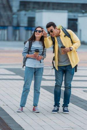Photo pour Homme biracial pointant avec le doigt près de la femme de sourire avec le sac à dos et la tasse de papier de café - image libre de droit