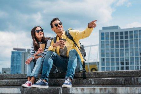 Photo pour Touriste mélangé de course avec la cuvette de café s'asseyant sur des escaliers près de la femme et pointant avec le doigt - image libre de droit