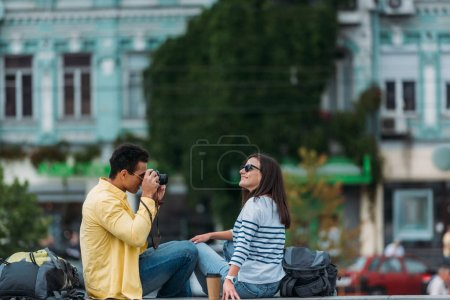 Photo for Bi-racial man sitting and taking photo of woman in sunglasses with backpack - Royalty Free Image