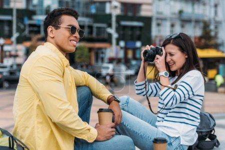 Photo pour Femme s'asseyant et prenant la photo de l'homme multiracial dans des lunettes de soleil et la tasse de café - image libre de droit