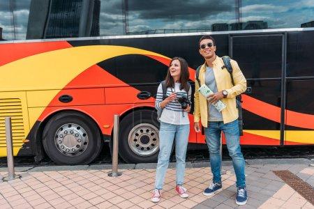 Photo pour Homme mélangé de course avec la carte et la femme avec l'appareil-photo numérique près du bus de voyage - image libre de droit