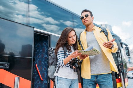 Photo for Woman with digital camera looking up on map with mixed race man near travel bus - Royalty Free Image