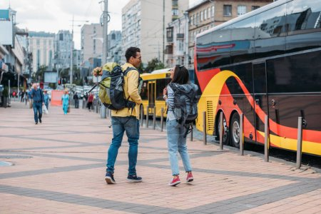 Back view of travelers with backpacks near travel bus