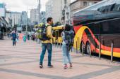 """Постер, картина, фотообои """"Back view of travelers with backpacks near travel bus"""""""
