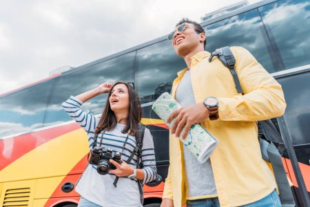 Photo for Woman holding digital camera and looking away with mixed race man holding map near travel bus - Royalty Free Image