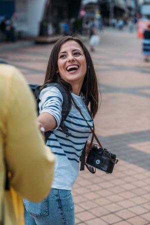 Photo pour Voyageur féminin avec l'appareil-photo numérique et le sac à dos retenant la main et le sourire - image libre de droit