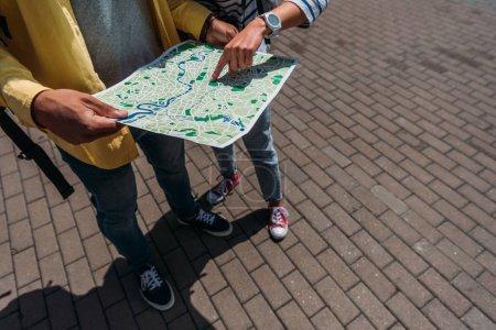 Photo pour Vue cultivée des voyageurs restant sur la rue et pointant avec le doigt à la carte - image libre de droit