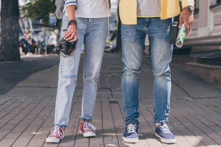 Photo for Partial view of tourists in jeans with digital camera and map - Royalty Free Image