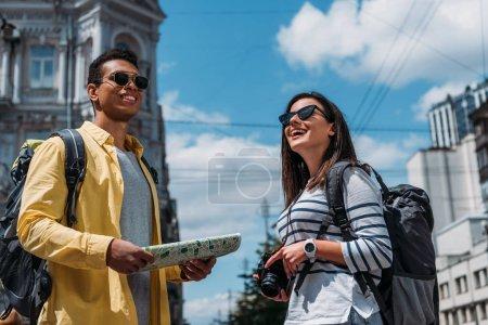 Photo pour Femme en lunettes de soleil avec appareil photo numérique proche ami bi-racial avec carte et sac à dos - image libre de droit