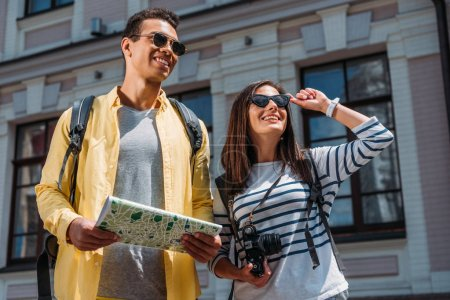 Foto de Mujer con cámara digital turismo cerca de amigo bi-racial con mapa y mochila - Imagen libre de derechos