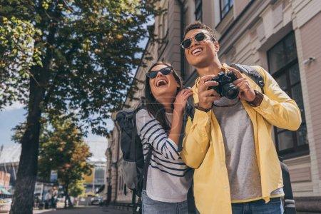 Photo pour Femme et ami bi-racial avec des sacs à dos souriant et prenant des photos - image libre de droit