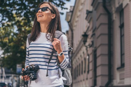 Photo for Happy woman in sunglasses with backpack holding digital camera - Royalty Free Image