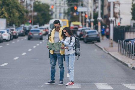 Foto de Mujer y amigo multirracial con mochilas sosteniendo el mapa de la ciudad en el paso de peatones - Imagen libre de derechos