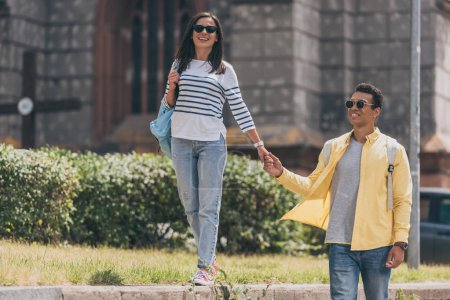 Photo for Multiracial man in sunglasses with woman holding hands and walking - Royalty Free Image