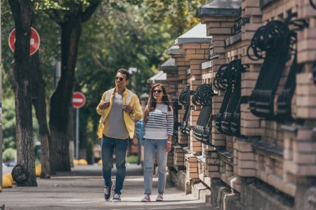 Photo for Bi-racial man in sunglasses near woman walking with backpack - Royalty Free Image