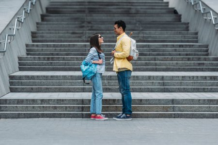 Photo for Woman standing in front of stairs and looking at bi-racial friend with backpack - Royalty Free Image