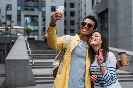 Bi-racial man in sunglasses with woman taking selfie on smartphone