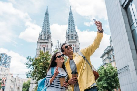 KYIV, UKRAINE - JULY 8, 2019: Woman near bi-racial man in sunglasses taking selfie on smartphone