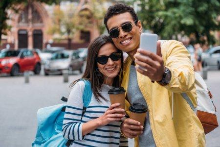Photo pour Homme biracial prenant le selfie avec la femme retenant la cuvette de papier - image libre de droit