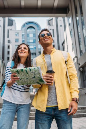 Smiling bi-racial man with paper cup near woman holding map