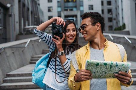 Foto de Mujer tomando fotos en la cámara digital y mirando a amigo bi-racial sosteniendo mapa - Imagen libre de derechos