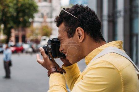 Foto de Multiracial man taking photo on digital camera in city - Imagen libre de derechos