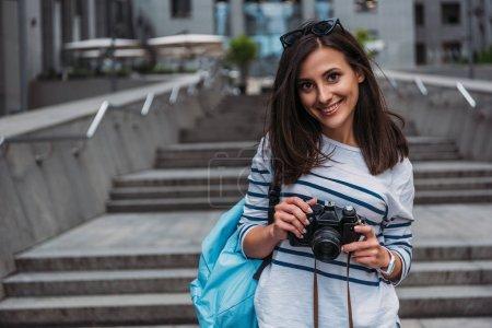 Photo pour Femme décontractée avec sac à dos tenant appareil photo numérique et souriant - image libre de droit