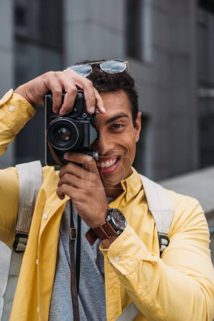 Photo for Portrait of multiracial man taking photo on digital camera - Royalty Free Image