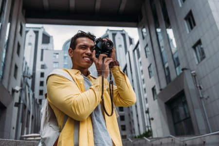 Photo for Bi-racial man taking photo on digital camera near buildings - Royalty Free Image