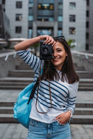 Photo for Happy girl taking photo on digital camera and standing with hand in pocket outside - Royalty Free Image