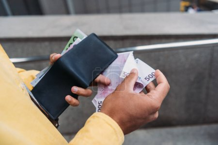 cropped view of mixed race man holding wallet and counting euro banknotes