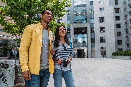 Photo pour Femme heureuse et homme métis debout près du bâtiment - image libre de droit