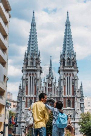 Foto de KYIV, UCRANIA - 8 de julio de 2019: felices amigos multiculturales cerca de la Catedral Católica Romana de San Nicolás - Imagen libre de derechos