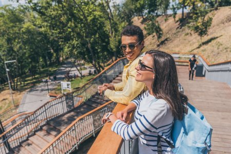 happy mixed race man looking at girl in sunglasses