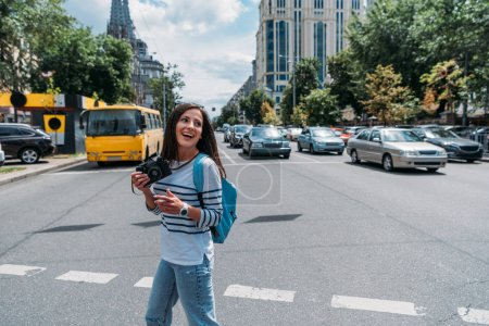 happy girl holding digital camera while standing on street with cars